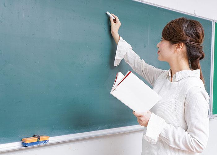 黒板に書く女性教師